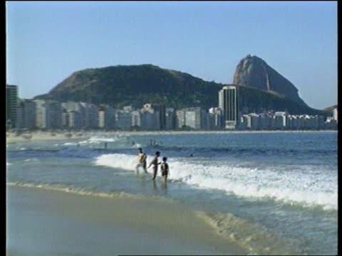 vidéos et rushes de nike itn brazil rio de janiero ext sugar loaf mountain pull out beach people on beach boy playing football on the beach children playing football on... - brésil