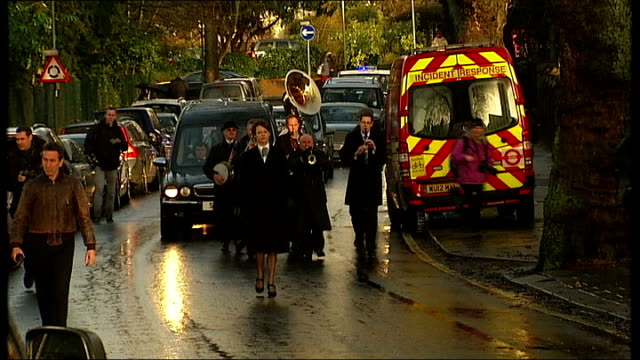 ronnie biggs funeral **music heard sot** people along / brass band playing 'when the saints go marching in' as along in front of hearse during... - hearse stock videos & royalty-free footage