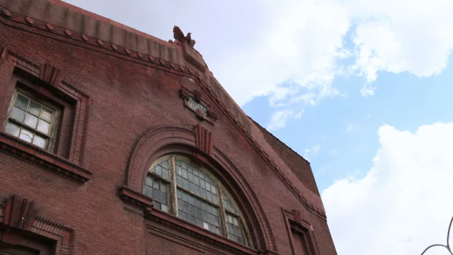 MS Roof and arched windows of red brick building beneath a blue sky / Philadelphia, Pennsylvania, United States