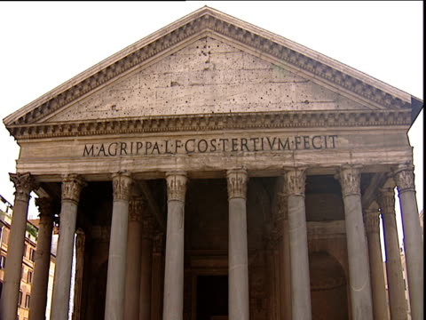 roof and latin inscription on pantheon tilt down to high pillars and tourists on cobbled street below rome - pantheon rome stock videos and b-roll footage
