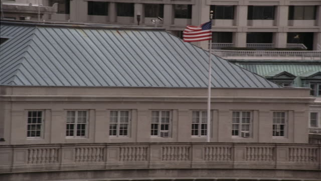 pan roof of national archives building with american flag waving in the breeze / washington, d.c., united states - national archives washington dc stock videos and b-roll footage