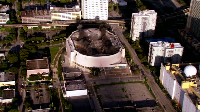 vidéos et rushes de ws aerial zi roof of  small sports arena is demolished using explosives / miami, florida, usa - imploding