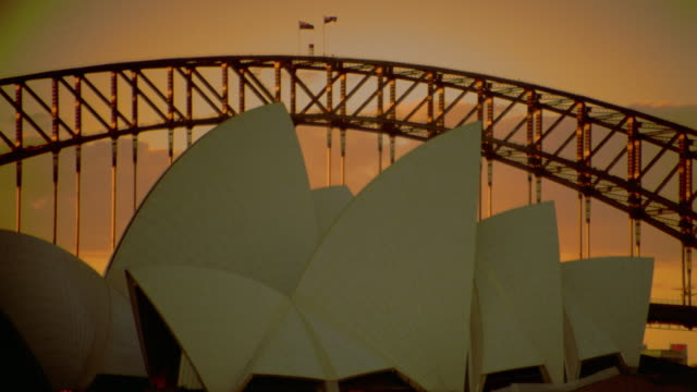 PAN roof of Sydney Opera House + harbor bridge at sunset / Sydney, Australia