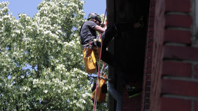 roof renovation. manual worker use safety harness and safety line  and working on a roof repair - safety harness stock videos & royalty-free footage