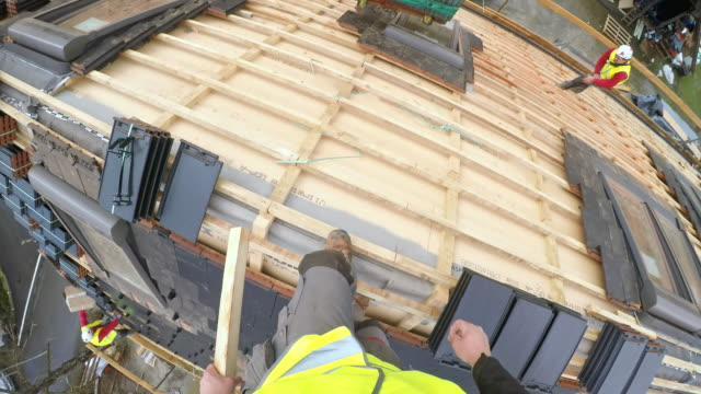 pov roof worker standing on the roof ridge and looking down - construction worker stock videos & royalty-free footage