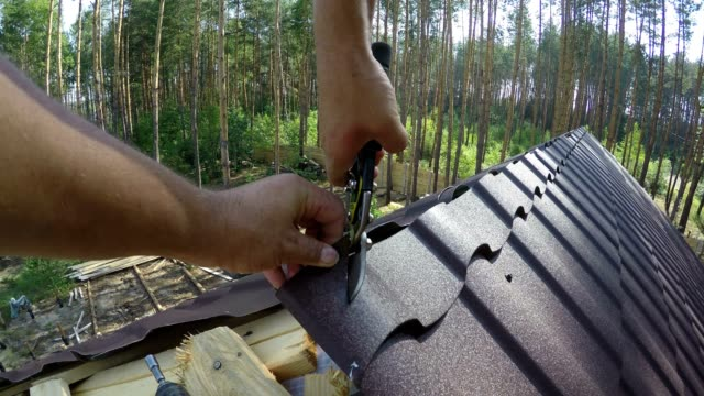 roofer cuts roofing metal material. - roof tile stock videos & royalty-free footage