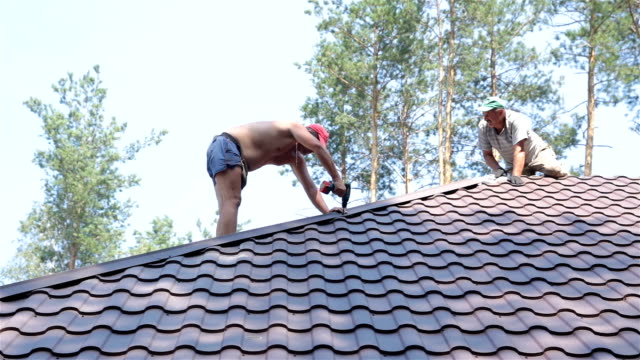 roofer fastens metal roofing material to the corners of the roof. - construction material stock videos & royalty-free footage