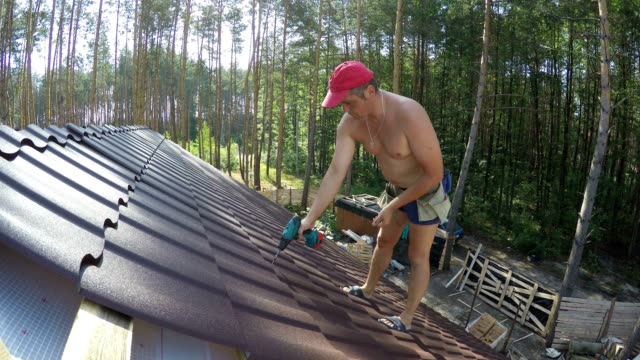 roofer fastens metal roofing material with screws. - roof tile stock videos & royalty-free footage