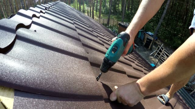 roofer fastens metal roofing material with screws. - construction material stock videos and b-roll footage