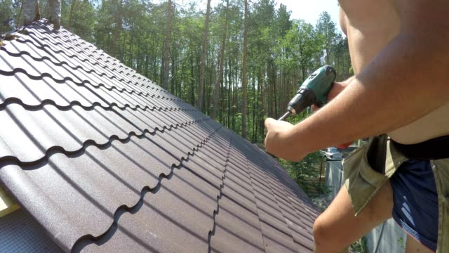 Roofer fastens metal roofing material with screws.