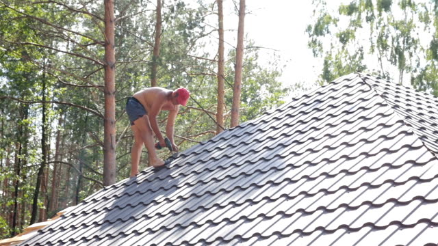 Roofer fixes the metal roofing material on the roof.