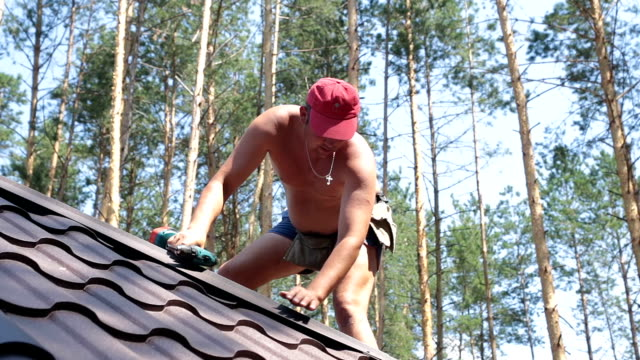 roofer installs the metal roofing material. - construction material stock videos and b-roll footage