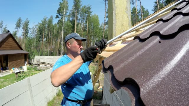 roofer makes measurements of the roof. - rooftop stock videos & royalty-free footage