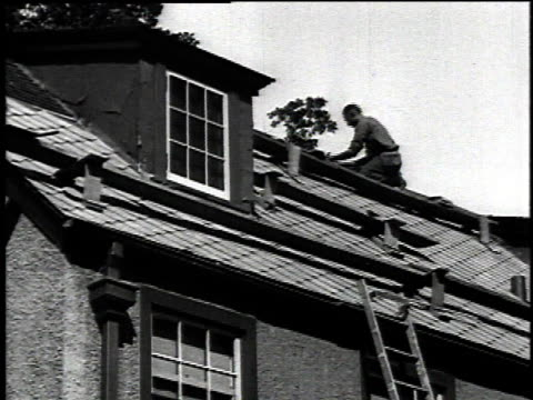 1921 montage roofer nailing down shingles to roof of house / united states - 1921 stock-videos und b-roll-filmmaterial