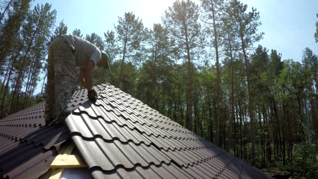 roofer puts the metal roofing material on the roof. - rooftop stock videos & royalty-free footage