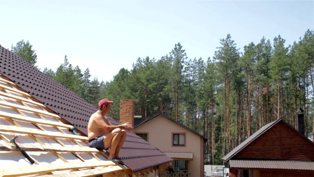 roofer sits on the roof. - roof top stock videos and b-roll footage