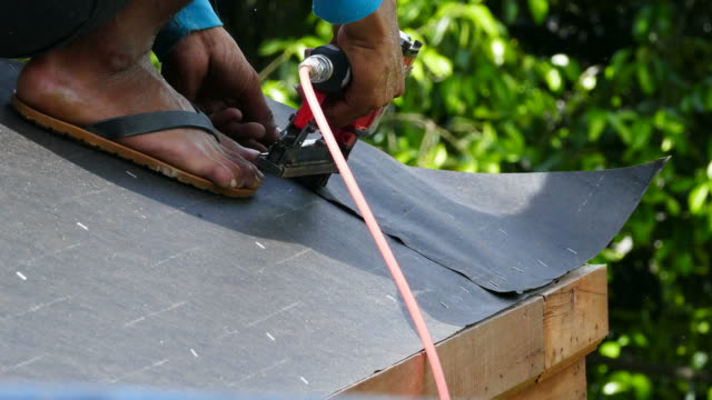 Roofer works on the roof