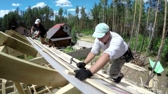 roofers are hammering nails into a plank on the roof. - hammer stock videos and b-roll footage