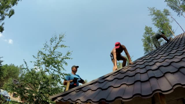 roofers fasten metal roofing material to the corners of the roof. - construction material stock videos & royalty-free footage