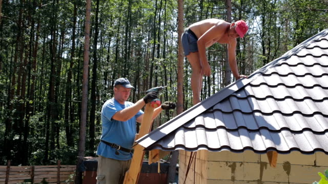 Roofers fasten metal roofing material to the corners of the roof.