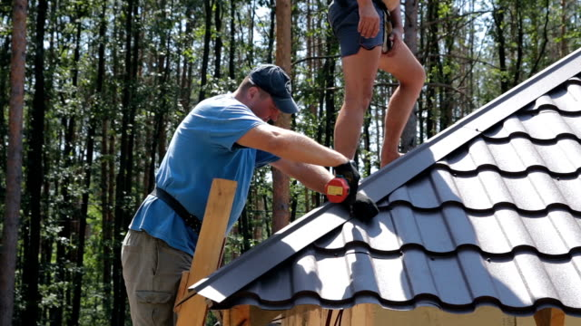 Roofers fasten metal roofing material.