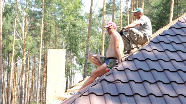 Roofers rest on the roof.
