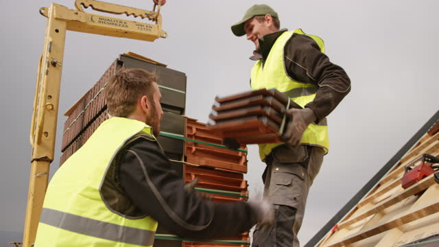 roofers unloading a pallet of tiles on the rooftop - tile stock videos & royalty-free footage