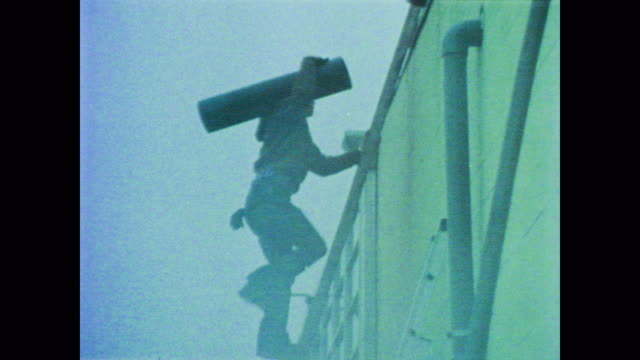 stockvideo's en b-roll-footage met 1978 roofers work as narrator john wayne explains high incidents of cancer in roofers - documentairebeeld