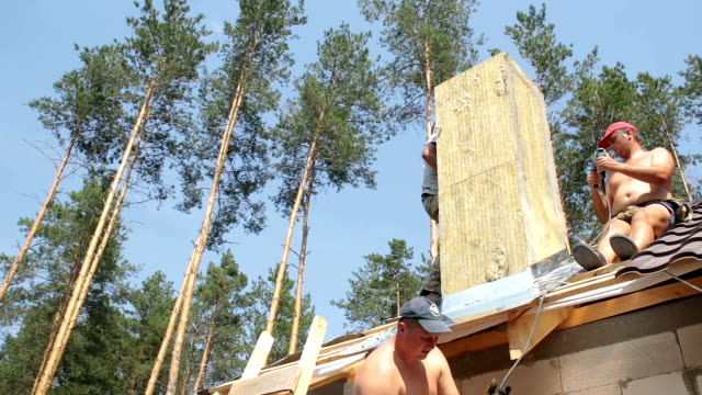 屋根葺き職人は煙突近くの屋根の上に動作します。 - ドリルビット点の映像素材/bロール