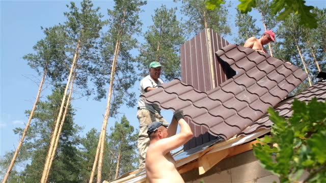 Roofers work on the roof near the chimney.