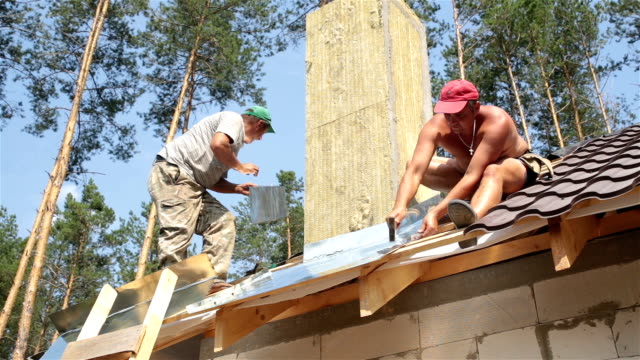 roofers work on the roof. - drill stock videos & royalty-free footage