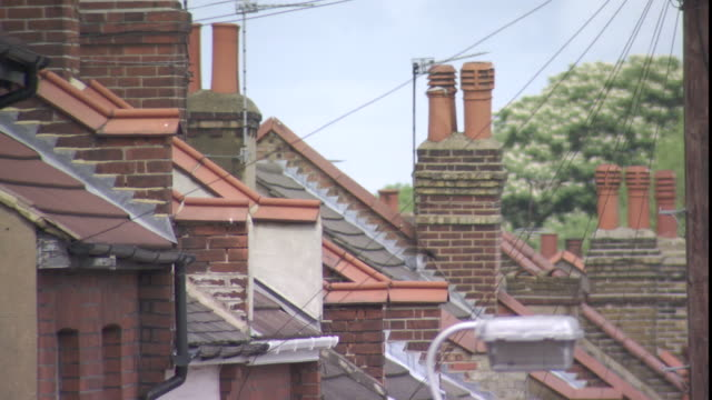 CU TU TD Roofs of old-style apartment buildings with many chimneys and satellite dishes / London, London, UK