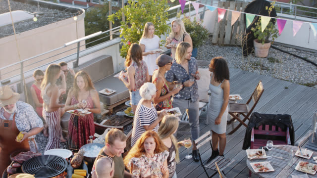 rooftop bbq party - crowd of trendy and stylish people enjoying themselves on a roof-deck while sunny summer day. - patio stock-videos und b-roll-filmmaterial