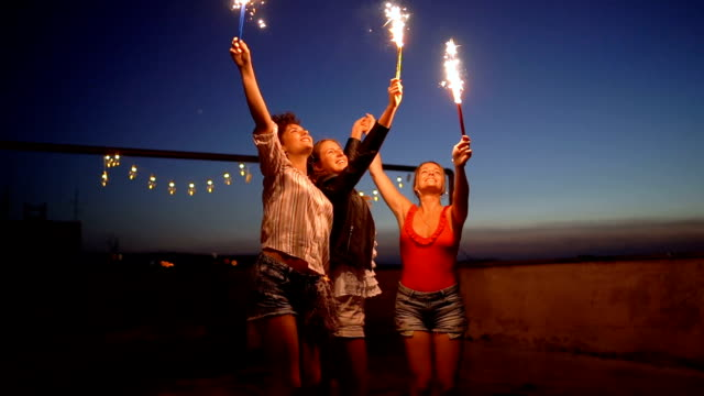vídeos de stock e filmes b-roll de rooftop party friends with sparklers - crepúsculo