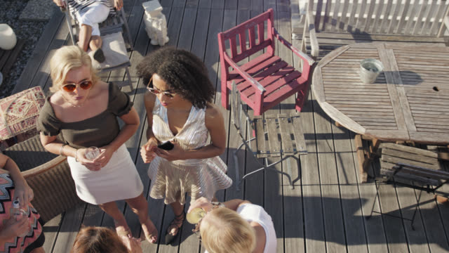 vidéos et rushes de rooftop party - stylisch co-workers chatting and enjoying themselves while office party on a roof deck on sunny summer day. - terrasse