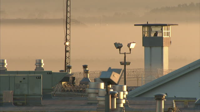*Rooftop WS Silhouette of prison guard in tower fencing w/ razor wire lights radio tower at roof edge mist BG Correctional facility incarceration not...