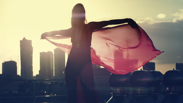 vídeos de stock e filmes b-roll de rooftop sunset. seductive woman in elegant dress playing with silken scarf - seda