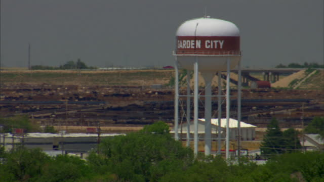 rooftop view of 'garden city' water tank tower treetops fields warehouse buildings highway in the distance on overcast day - kansas stock videos & royalty-free footage