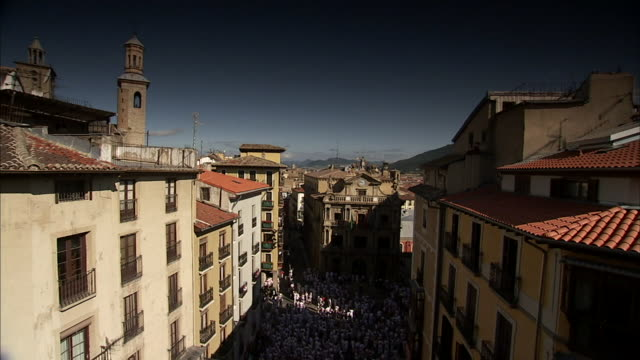 rooftop view of massive crowd in square below between rows of buildings and town hall building in bg during the chupinazo opening of the san fermin... - comunidad foral de navarra stock videos and b-roll footage
