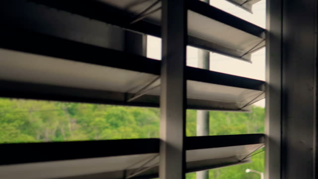 A rooftop view through the vent grid to green forest and mountains near to city with electric poles in raining day. Escape and hide.