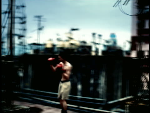 high contrast pan rooftop with fences + antennae to male boxer practicing on roof / hong kong - high contrast stock videos & royalty-free footage