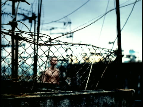 high contrast pan rooftop with fences + antennas to asian male boxer walking toward camera / hong kong - high contrast stock videos & royalty-free footage