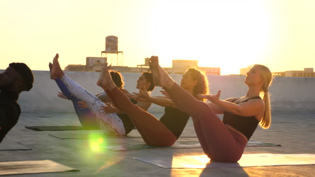 ms rooftop yoga class in boat pose - leggings stock videos & royalty-free footage