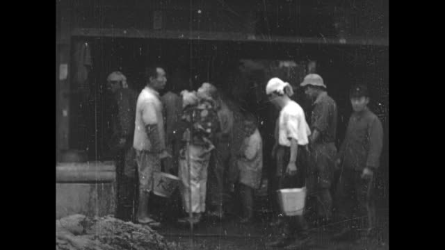 rooftops above high water / vs line of people with buckets flowing water people carrying the heavy pails away / people digging through large piles of... - 1940~1949年点の映像素材/bロール