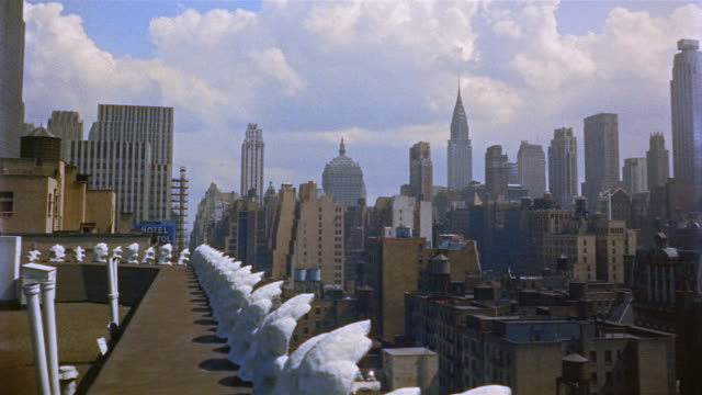 1954 MONTAGE rooftops and skyline of midtown Manhattan / Chrysler Building visible in background / New York City