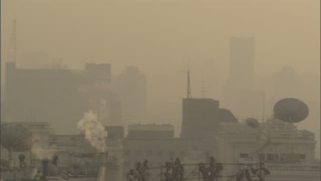 ms pan rooftops and skyline through thick haze of smog and smoke, beijing, china - smog stock-videos und b-roll-filmmaterial