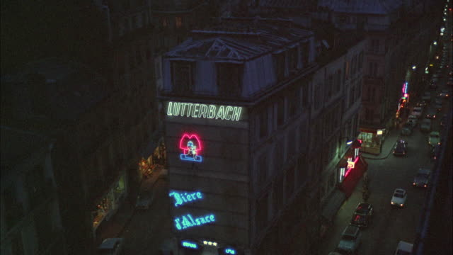 1966 WS HA Rooftops and street at night, building with neon in foreground / London, United Kingdom