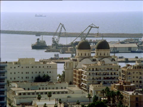 vídeos de stock, filmes e b-roll de rooftops domes and harbour in foreground with boats and cranes behind port of benghazi - líbia