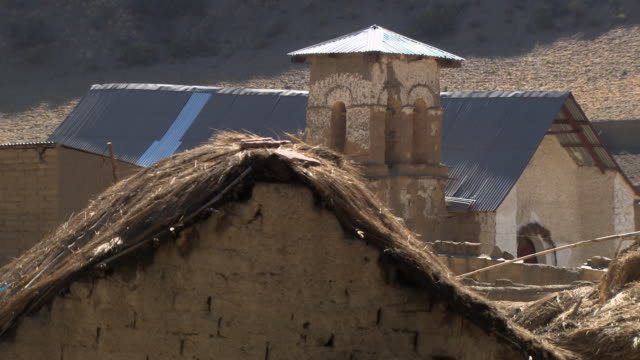 Rooftops made from various materials straw, corrugated iron, small church belltower in disrepair, in small rural town, Potolo, Bolivia