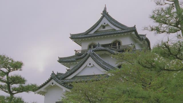 vídeos y material grabado en eventos de stock de d/x rooftops of nagoya castle above treetops, japan - castillo estructura de edificio